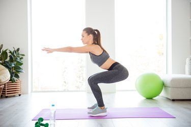 Athletic woman doing squats for a rounder butt
