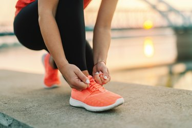 Close up of a person tying an orange sneaker, to illustrate wearing shoes that fit well to prevent ingrowns