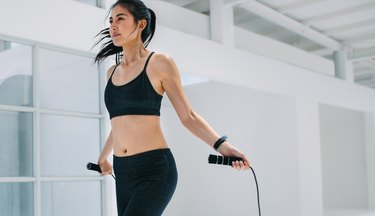 Woman doing fitness training with jump ropes
