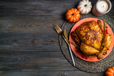Baked turkey for Thanksgiving Day. Roasted whole chicken or turkey with herb rosemary and berries for thanksgiving dinner on wooden table. Festive table settings for Thanksgiving Day