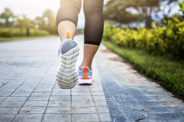 View of a woman's feet as she runs in the park, trying to lower her blood pressure