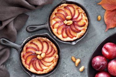 Homemade crumble tarts with plum slices baked in small iron skillets