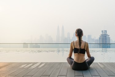 Woman in yoga clothes meditating outside