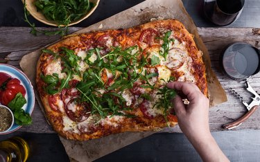 Preparing gourmet pizza, close-up of hand topping pizza with arugula