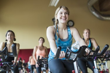 Smiling women cycling on exercise bikes at gym