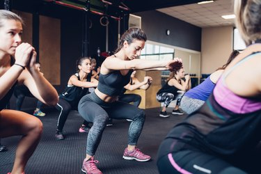 Group of women training in gym, squatting