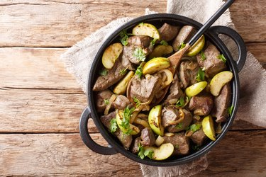 German food fried beef liver with green apples and onions close-up in a pan. Horizontal top view