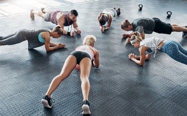 A group of people doing abdominal planks at the gym