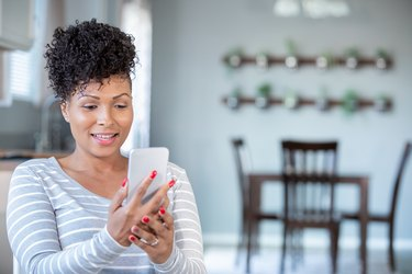 woman uses smartphone for telemedicine appointment with doctor at home
