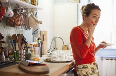 A woman eating a snack in the kitchen because she's still hungry
