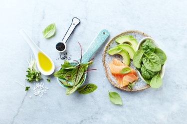 Ingredients for a healthy salad on gray stone background. Smoked salmon, avocado, spinach, sorrel, radis sprouts, black cumin. Flat lay. Healthy diet. Symbolic image.