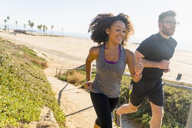 Couple runnExertion Headaches: A Pain, but Probably Not Dangerousing along pathway by beach
