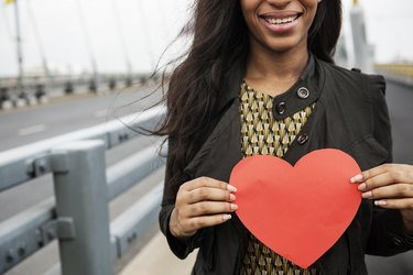 A smiling African-American woman holding a red paper heart