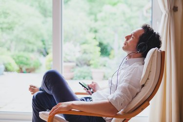 A man sitting at home in a chair wearing headphones and doing guided imagery meditation