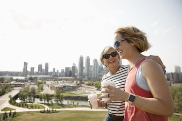 Smiling mother and daughter walking in sunny urban park with coffee