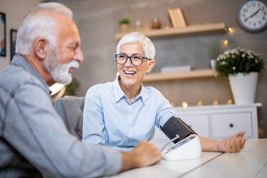 Senior couple checking their blood pressure.