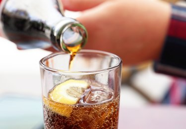 Hand pouring cola soda drink from bottle to glass not knowing how much sugar in coke