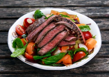 Slices of medium steak over a salad with mixed vegetables
