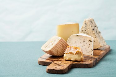 Variety of cheeses on serving board for a low-carb diet
