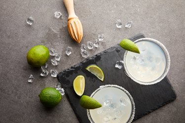 Top view of margarita cocktails with pieces of lime, ice cubes and wooden squeezer on grey tabletop
