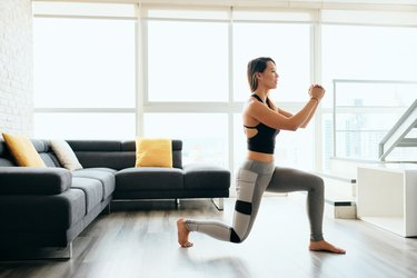 woman wearing leggings and tank top doing lunges in her living room