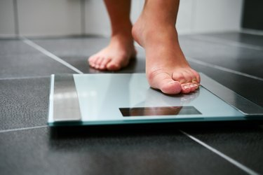 A woman's bare feet stepping onto a digital scale in her bathroom at home