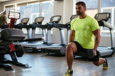 photo of man in gym in front of treadmills doing lunges holding dumbbells