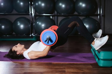 fit woman doing a barbell hip thrust on a purple yoga mat and step