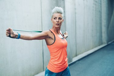 Modern sportswoman exercising with resistance band to increase bone density