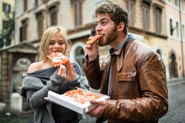 couple eating a pizza in italy not practicing how to how to eat healthy on vacation.