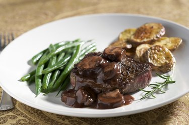 A white plate with a piece of steak with Mushroom Wine Sauce and Vegetables