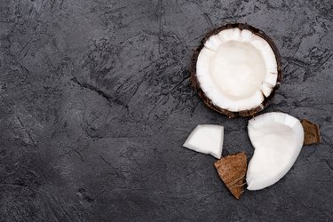 Top view of fresh healthy broken coconut on black background