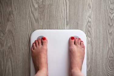 Woman stands on white modern electronic sensor scales. Only feet are visible. Scales stand on gray wooden floor. Space for text. Healthy lifestyle, diet, weight loss concept. Horizontal.