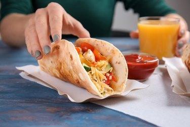 Woman eating tasty taco at table, closeup