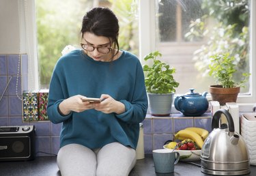 Woman using weight-loss incentive app on her phone, while sitting on the kitchen counter next to a tea kettle