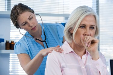 Doctor examining coughing patient