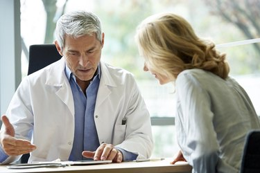 Doctor consulting patient in clinic about pain in upper left abdomen