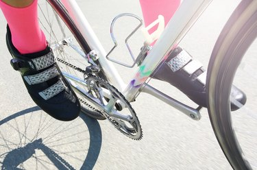Woman cycling in pink socks and black cycling shoes