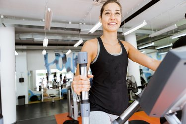 Young fit woman using an elliptic trainer