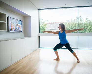 Woman exercising at home watching a workout video