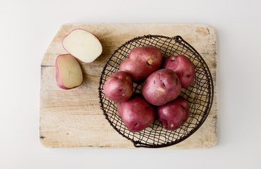 Red potatoes in wire basket on cutting board.