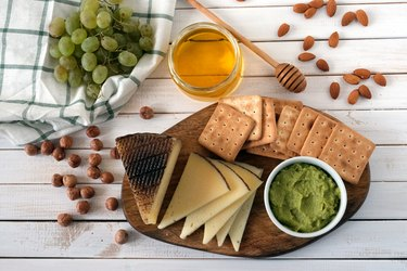 Cheese served with grapes, guacamole, honey, crackers and nuts on a light wooden background. Top view