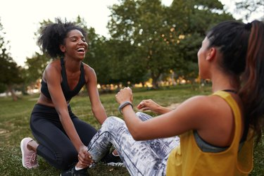 Cheerful young diverse female friends laughing doing ab crunches on green grass in the park - friends laughing together while doing exercise outdoors