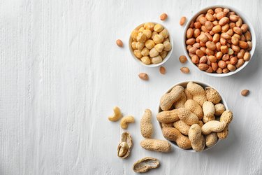 Flat lay composition with different kinds of nuts on light background
