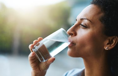 woman drinking water, as a natural remedy for upset stomach
