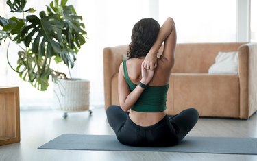 Young woman enjoying her morning yoga at home, back view. Cow head pose