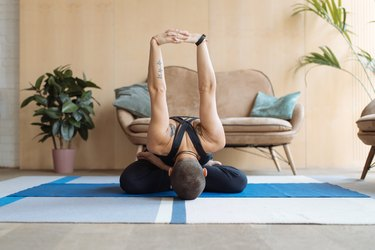 short haired woman practicing yoga lotus pose in home loft interior