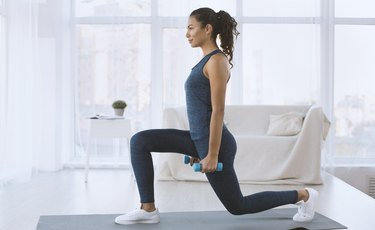 Woman doing lunges with dumbbells at home to strengthen her quads