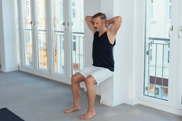 Middle-aged man exercising wall sit for legs