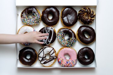 Doughnut Box with Young Girl's Hand Grabbing One